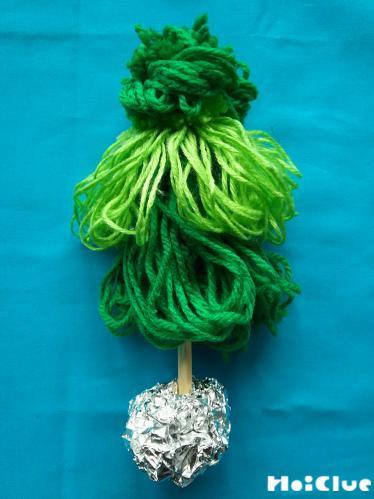 割り箸に毛糸を3段に差し込み、底にアルミホイルを巻いた様子