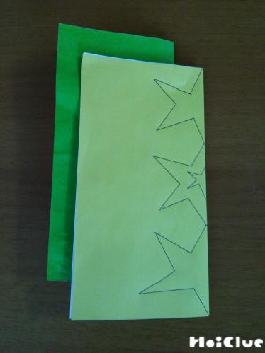 半分に折った折り紙の輪の方に星型を描いた様子