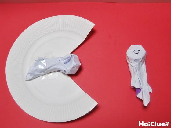 天使の顔を作り残りの紙皿に貼り付ける様子