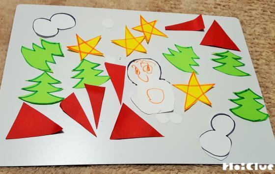 画用紙に描いたクリスマスの絵を切り取った写真