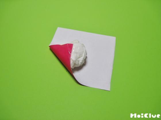丸めたティッシュを折り紙で包む様子