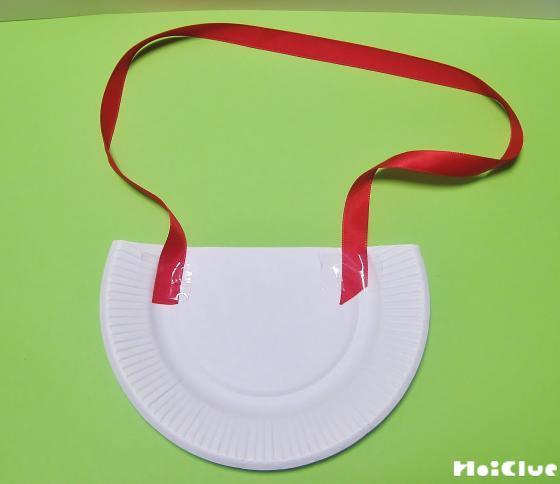 紙皿の裏側にバッグの持ち手となるリボンを貼った写真