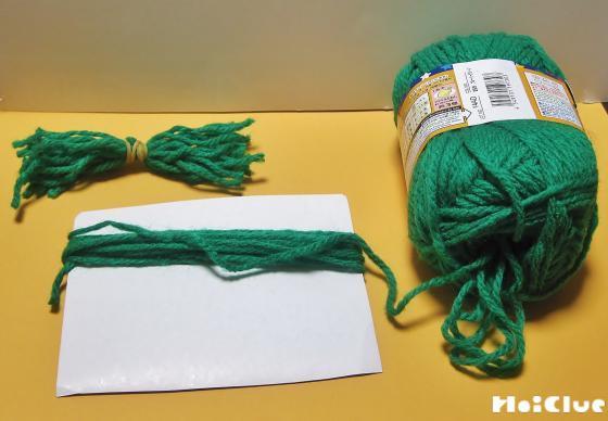 緑色の毛糸を紙に巻きつけている写真
