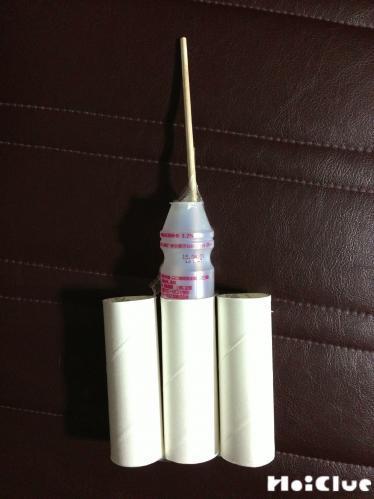 トイレットペーパーの芯を横に3個つなぎ合わせ、真ん中の芯の上に乳酸菌飲料の容器と割り箸を固定した様子