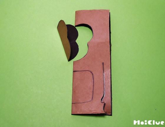 中表に折った紙の顔部分を切り抜き、手部分に切り込みを入れた様子