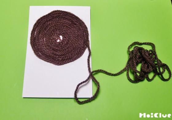 年賀状に毛糸をうず巻状に貼り付けていく様子
