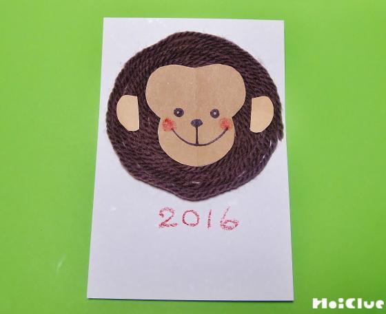 毛糸の上に猿の顔と耳のパーツを貼って完成した年賀状の写真
