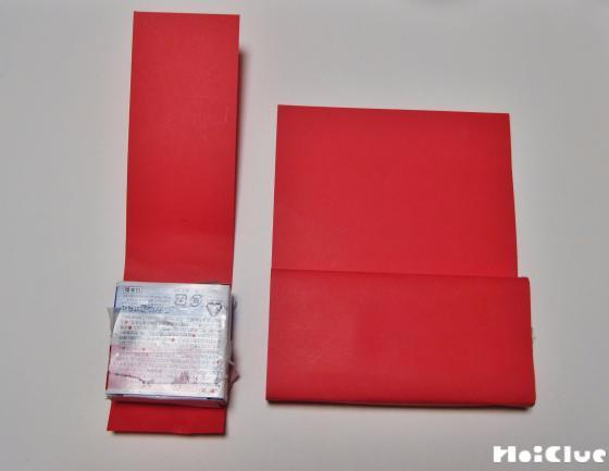 赤い色画用紙を細く切ったものを箱を包んでいる写真