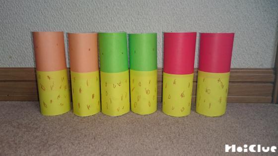 トイレットペーパーの芯の上下にそれぞれ別の色の折り紙を巻いた写真
