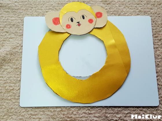 折り紙を貼ったドーナツ型の上に猿の顔を貼った写真
