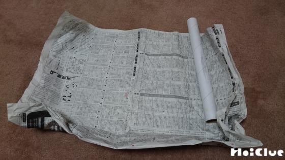 広げた新聞紙の上にラップの芯を固定する様子