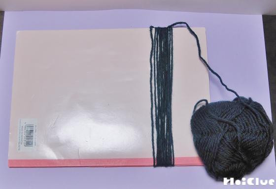 ノートに毛糸を巻きつけて長さを整えている写真