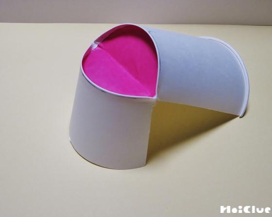 紙コップの底に赤い折り紙を貼り、底面を谷折りにした写真