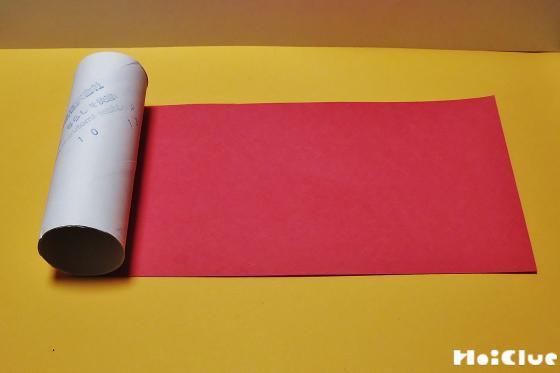 赤い画用紙の上にトイレットペーパーの芯を置いた写真