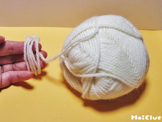3本の指に毛糸を巻く様子