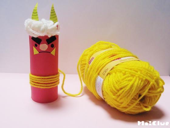 トイレットペーパーの芯の下の方に黄色い毛糸を巻きつける様子