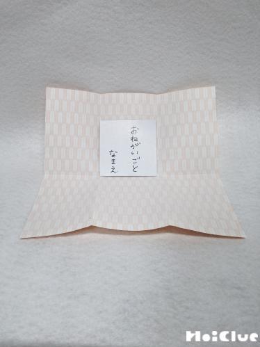 開いて中にお願い事を書いた紙を入れている写真
