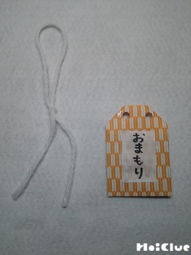 カットした毛糸とお守りの写真