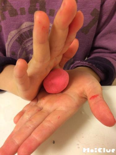 紙粘土を両手の平で丸める様子