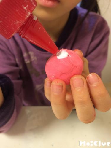 丸くした紙粘土の上に開けた穴にボンドを入れる様子