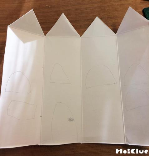 牛乳パックを切りドアや屋根を描いている写真