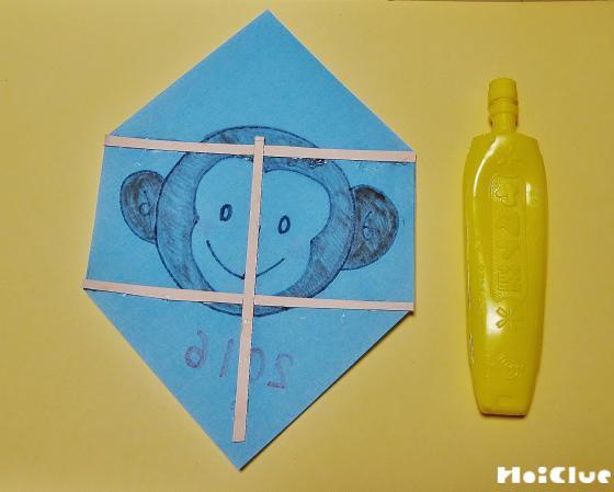 折り紙の色の面に細く切った厚紙を貼っている写真