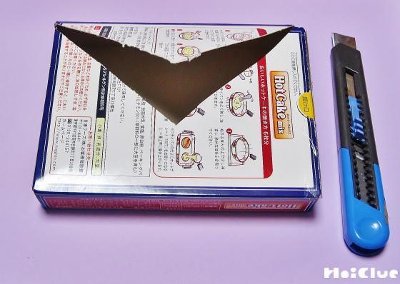 空き箱の裏面にカッターで三角形の切り込みを入れる様子
