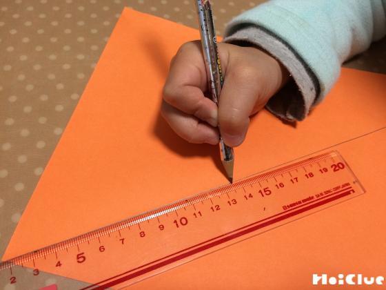 画用紙に定規を当て線を引く子どもの様子