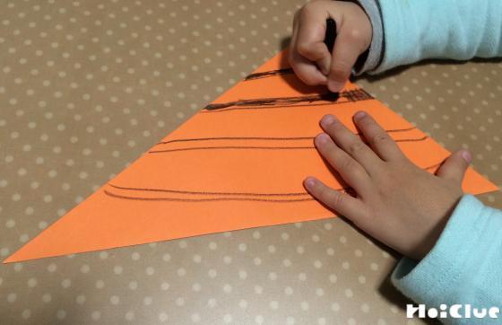 三角形に切り取った画用紙に縞模様を描く子どもの様子