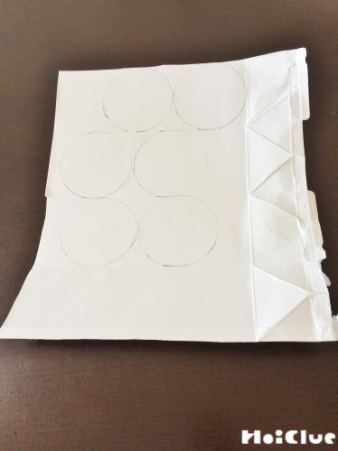 開いた牛乳パックに丸を6個描いた写真
