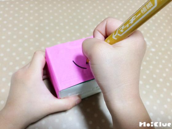 牛乳パックに折り紙を貼り絵を描く様子