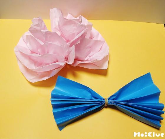 蛇腹折りにし中心を輪ゴムで留めた青い花紙と、同様に作ったピンクの花紙を花のように開いた写真