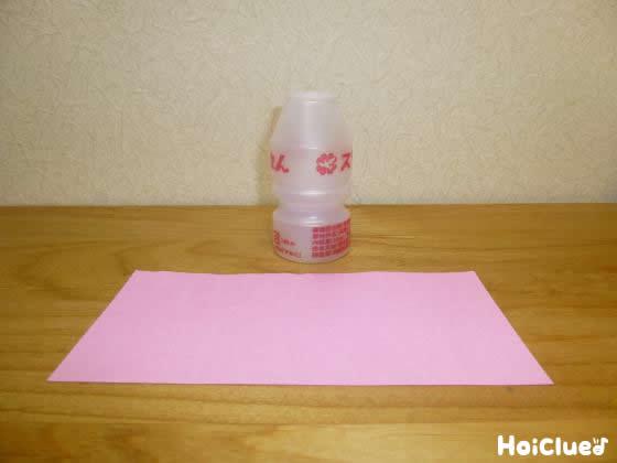 折り紙と乳酸菌飲料の容器の写真