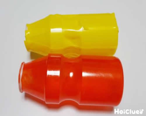 赤と黄色に色を付けた2個の乳酸菌飲料の容器