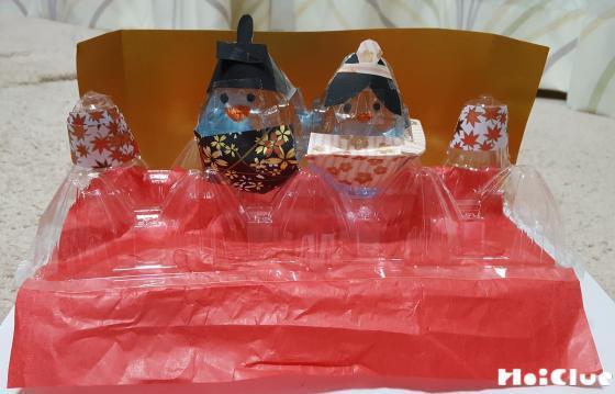 赤い紙を挟んだ卵パックをひな壇にみたてて作成したお雛様を飾り付けた写真