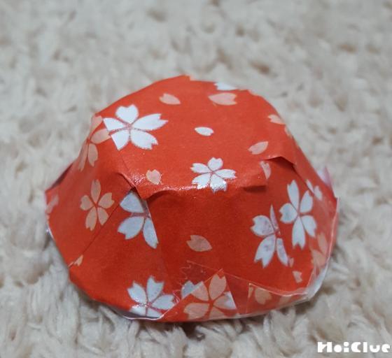 卵パックの1個分を切り取り折り紙を貼りお皿を作る様子