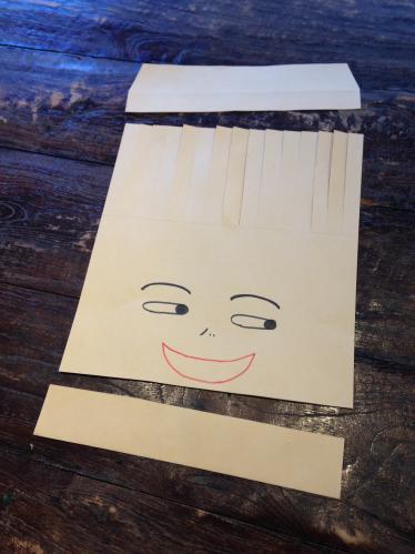 紙袋に顔を描き上下を切り取って前髪の部分に切り込みを入れた写真