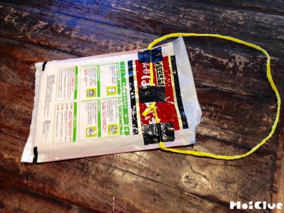 米袋にガムテープでスズランテープを取り付けた写真