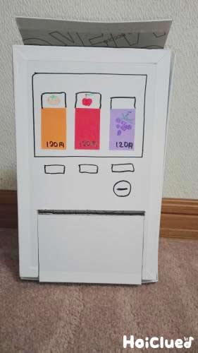 箱に芯で作った飲み物の絵やボタンを描いた様子