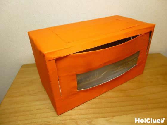箱全体をオレンジ色の折り紙で覆った写真
