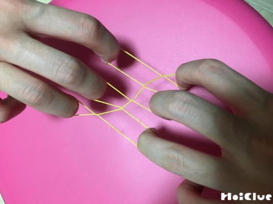 両手の指に輪ゴムを引っかけて引っ張る様子