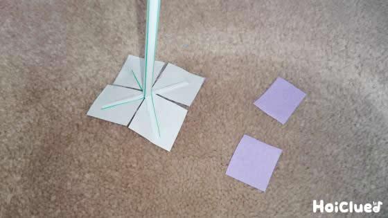 四角に切った折り紙をストローの切り込みの所に貼り付けている写真