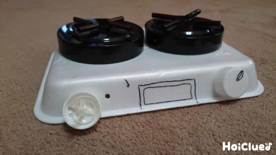 発泡スチロールトレーの側面にペットボトルキャップを2個貼り付け完成したコンロの写真