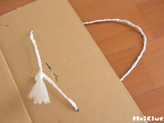 ダンボールに穴を開けて紐を通した写真