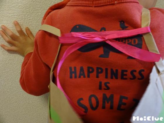 子どもの肩に紐で結んでいる写真