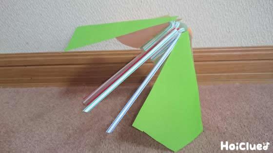 折り紙を三角に切ってストローに貼り付けている写真