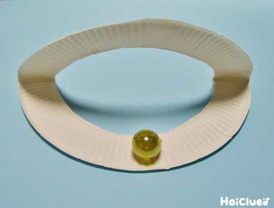 輪っかになった紙皿を半分に折り目をつけビー玉を貼り付けた写真