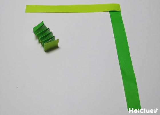 緑の折り紙を使って蛇腹折りにして足を作っている写真