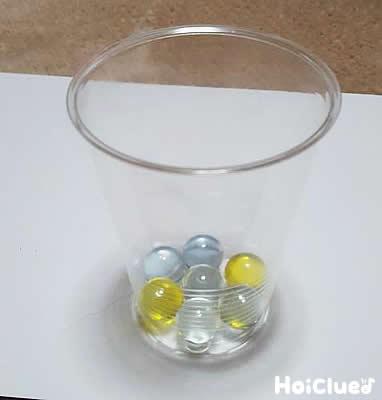 カップにビー玉を入れている写真