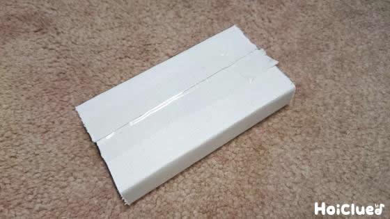 切り取った箱の部分を四角く折りリモコンを作る様子